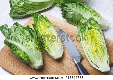 Romain lettuce on kitchen board - stock photo