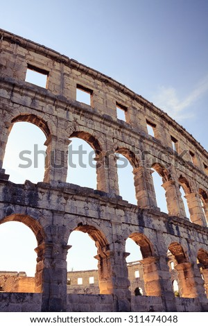 Roman amphitheater arena, theater and coliseum. Classic historical antique building. Tall wall with arches, ancient architecture. Travel destination, Istria at Adriatic Sea in Pula, Croatia - stock photo