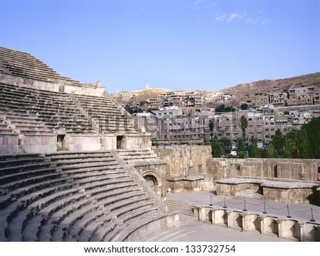 Roman amphitheater in Amman, at background the city of Amman in Jordan - stock photo