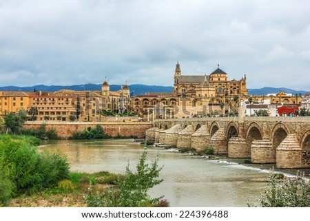 Roman Bridge on Guadalquivir river and Mezquita Cathedral (Great Mosque) at dawn in the city of Cordoba, Andalusia, Spain. - stock photo