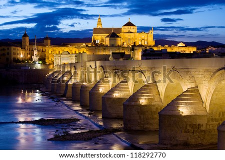 Roman Bridge on Guadalquivir river and Mosque Cathedral (La Mezquita) illuminated at dusk in the city of Cordoba, Andalusia, Spain. - stock photo