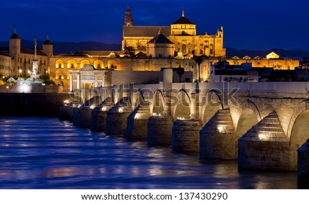 Roman Bridge on Guadalquivir river and The Great Mosque (Mezquita Cathedral) at twilight in the city of Cordoba, Andalusia, Spain - stock photo