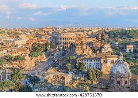 Roman Forum and Great Colosseum ( Coliseum, Colosseo, Flavian Amphitheatre ) in the evening,at sunset time.Scenic urban landscape. Aerial panoramic view on famous touristic landmark.Rome.Italy.Europe. - stock photo