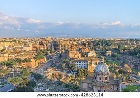 Roman Forum and Great Colosseum (Coliseum, Colosseo,Flavian Amphitheatre ) in the evening,at sunset time.Beautiful urban landscape.Aerial panoramic view on famous touristic landmark.Rome.Italy.Europe. - stock photo