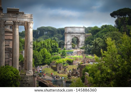 Roman Forum columns and the Arch of Titus in Rome, Italy  - stock photo