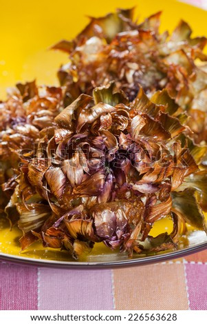 Roman fried artichokes to put to drain after cooking on a sheet of paper towel on a plate resting on a colorful tablecloth, fried twice