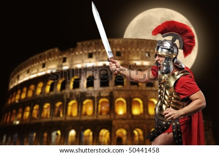 Roman legionary soldier in front of coliseum at night time - stock photo