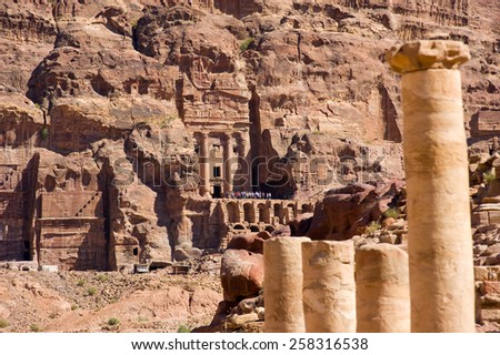 Roman pillars on the foreground, and the 'Urn tomb' from the royal tombs on the background in Petra in jordan - stock photo