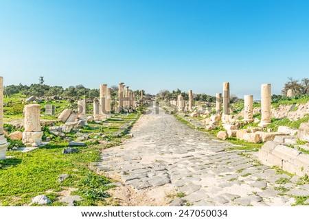 Roman Road at Umm Qais in northern Jordan. Umm Qais is a town in northern Jordan near the site of the ancient town of Gadara. - stock photo