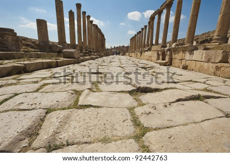 Roman road in Jerash, Jordan leading to the Oval Plaza, you can see ruts worn in the paving stones from the wheels of carts. - stock photo
