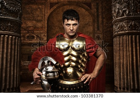Roman soldier against antique building. - stock photo