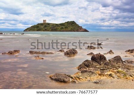 Roman tower on Island Sardinia Italy long exposure milky sea dramatic sky and clouds rocks in surf seascape and landscape