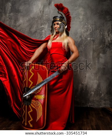 Roman warrior woman in red fluttering dress holds sword and shield. - stock photo