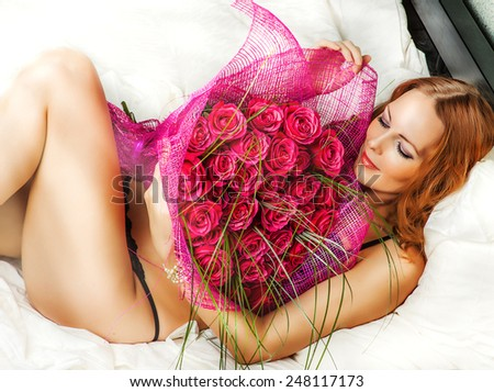 Romance. Beautiful young woman in bed with a big bouquet of red roses