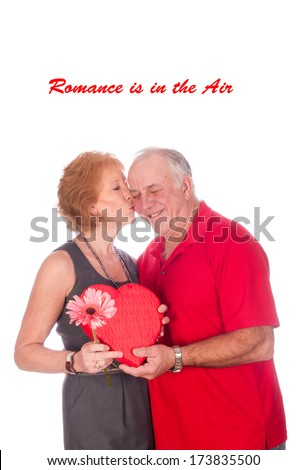 Romance is in the Air, an elderly couple embracing after the husband gave the wife flowers and chocolates - stock photo