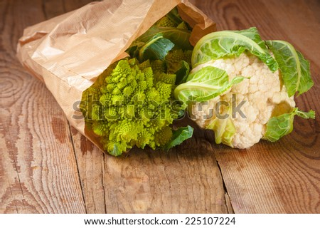 Romanesco broccoli and cauliflower in a paper bag on a wooden table and white background - stock photo