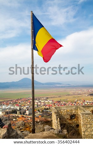 Romanian flag Romanian flag and part of old wall in Rasnov, Transylvania, Romania and town at the background - stock photo