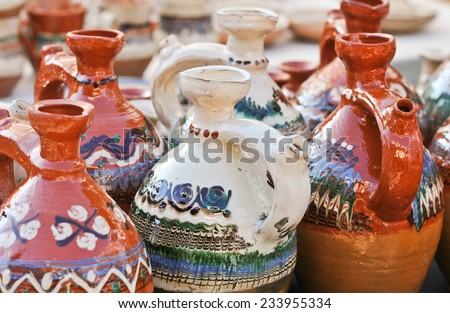 Romanian traditional pottery handcrafted mugs at a souvenir shop. Romanian traditional handcrafted pottery jugs to be sold at the market - stock photo
