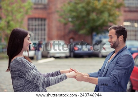 Romantic affectionate young man and woman out on a date standing in the street laughing and holding hands as they look into each others eyes - stock photo