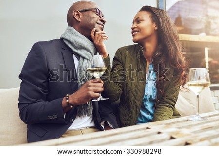 Romantic African American couple on a date flirting together at a restaurant table as they enjoy a glass of white wine - stock photo