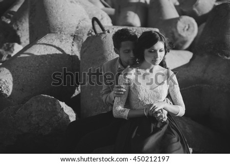 Romantic and stylish caucasian couple hugging at sunrise near the sea bay. Black and white image.