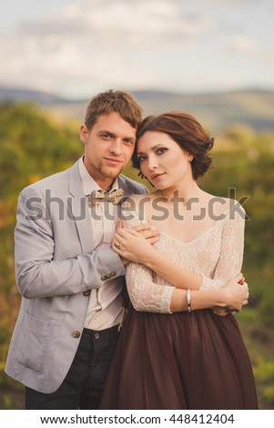 Romantic and stylish caucasian couple standing in the beautiful vineyard at sunset. Love, relationships, romance, happiness concept.