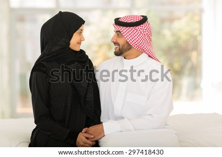 romantic arabic couple sitting on bed