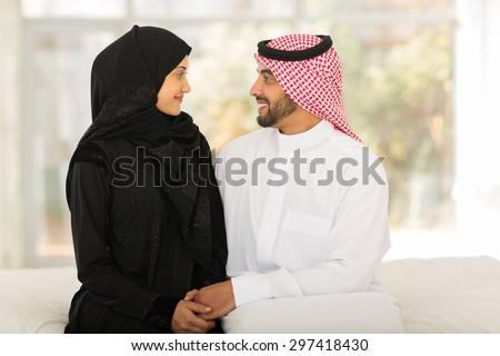 romantic arabic couple sitting on bed - stock photo