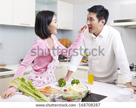 romantic asian couple preparing meal in kitchen.