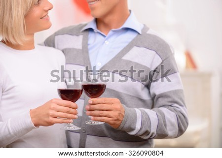 Romantic atmosphere. Agreeable loving adult happy couple holding glasses and drinking wine while bonding to each other - stock photo