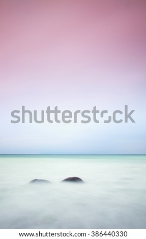 Romantic atmosphere in peaceful morning at sea. Big boulders sticking out from smooth wavy sea. Pink horizon with first hot sun rays.Vintage Style Toned effect - stock photo