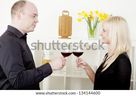 Romantic attractive man and woman standing sideways to the camera clinking their glasses of red wine in celebration toasting each other while looking into each others eyes with a smile - stock photo