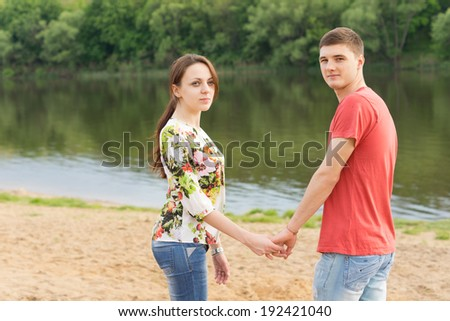 Romantic attractive young couple standing hand in hand on a sandy beach at a tranquil lake turning to look back at the camera with a friendly smile - stock photo