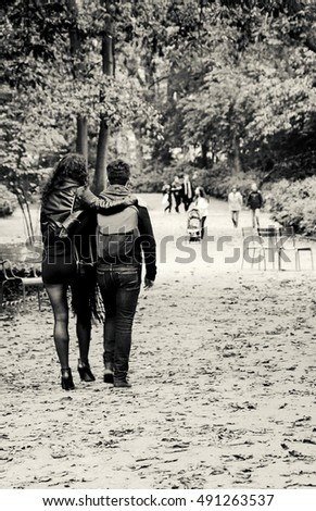 Romantic autumn in Paris. Luxembourg garden. Selective focus on couple in motion. Black and white.