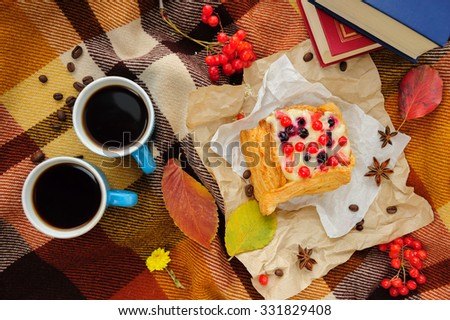 Romantic autumn still life with blanket, cake, book, coffee cups and leaves, top view - stock photo