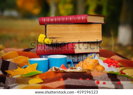 Romantic autumn still life with books, plaid, croissant, coffee cups and leaves