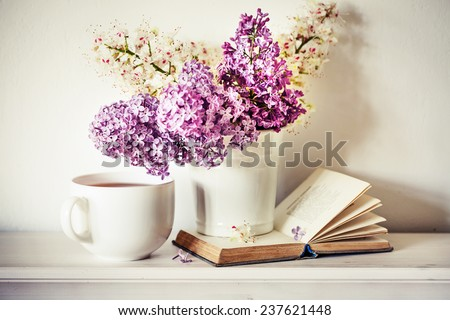Romantic background with cup of tea ,lilac flowers and open book over white table - stock photo