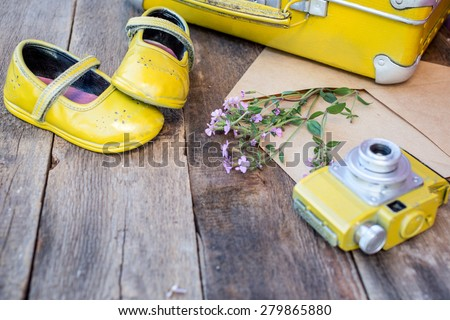 Romantic background with vintage things: camera, suitcase, old baby shoes, envelop with wild flowers over grunge brown background. selective focus  - stock photo