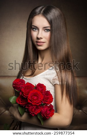 Romantic, beautiful, brunette female with bouquet of red roses her eyes with green make up are so hypnotizing. - stock photo