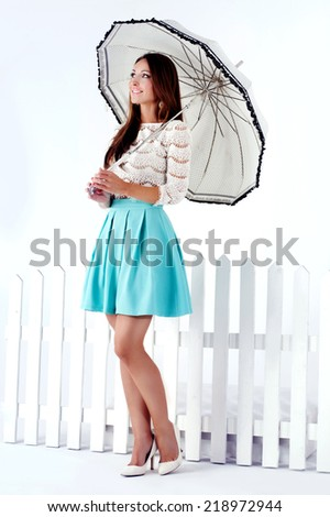 Romantic beautiful brunette woman standing with umbrella. Studio shot. - stock photo