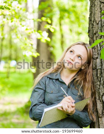 romantic beautiful girl writes love poems on nature - stock photo
