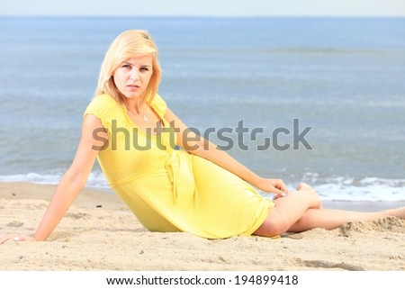 Romantic Beautiful smiling girl in the yellow dress water beach - stock photo
