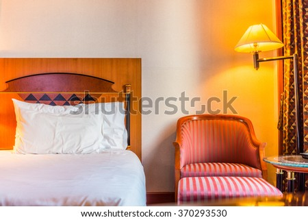 Romantic bed room and chair for relaxation. The room is in hotel room. - stock photo