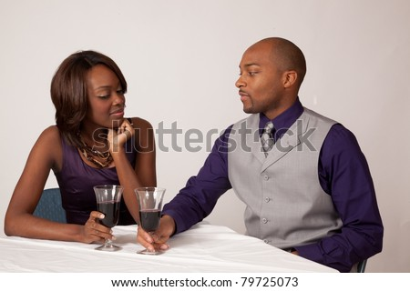 Romantic black couple drinking a glass of wine together