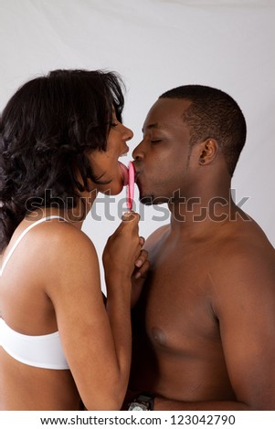 Romantic black couple in their underwear, with the a lollipop between them and both licking it - stock photo