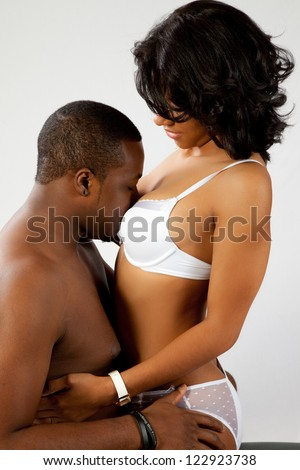 Romantic Black couple with the woman wearing a bra and panties, sitting in his lap and enjoying him kissing her chest - stock photo