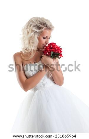 Romantic blond bride cuddles bouquet - stock photo