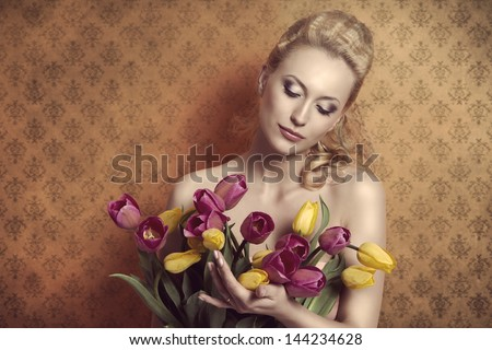 romantic blonde girl taking bouquet of colourful tulips in the hand, with pretty hair-style and naked shoulders. She looking the flowers  on vintage wallpaper - stock photo