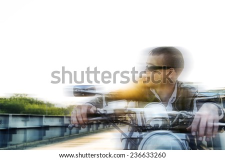 Romantic blur portrait handsome biker man in sunglasses sits on a bike on a sunset on old rusty metal bridge in city against house and sunny sky background Empty copy space for inscription - stock photo