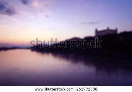 Romantic blurred background for website usage with Bratislava Castle and Danube River - stock photo